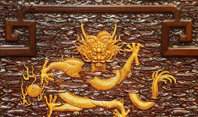 黄杨木雕刻的龙纹,镶嵌在浮雕云纹面板上,还非常巧妙的运用云纹遮掩住