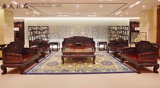 近年来,中式传统文化生活的回归,越来越多的人对中式古典红木家具开始着迷,红木家具的型、材、艺、韵都是其魅力的体现。宫廷红木家具作为家具传统家具的中的极品,展现出了无与伦比的尊贵。  区氏臻品展厅一角 宫廷红木家具,顾名思义就是皇宫中使用的红木家具。在我国封建社会,宫廷是国家权力的中心,拥有绝对的尊贵,所以在宫廷家具的制作上集能工巧匠,取稀世珍品之木,将中国家具制造的雕刻、榫卯、镶嵌、线脚等传统工艺展现得淋漓尽致。  区氏臻品展厅一角 宫廷红木家具在选材和用材上极其考究,一般会选用珍贵的黄花梨、紫檀等最上等