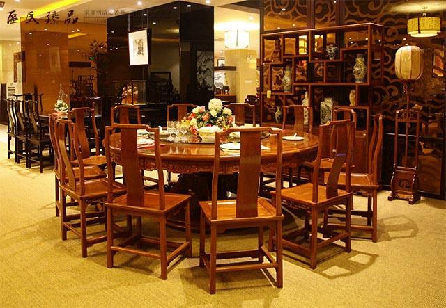红木圆桌,是中国红木家具中最常见的明清家具之一,也是中国家庭最喜欢的餐饮家具。当红木与圆桌相遇融合,随着台面的转动,人们对红木圆桌文化的遐想便延伸开来。如今,红木圆桌是中国红木家具中最常见的明清家具之一,也是中国家庭最喜欢的餐饮家具。当红木与圆桌相遇融合,随着台面的转动,人们对红木圆桌文化的遐想便延伸开来。  区氏臻品展厅一角 中式内涵:寓意团圆 圆桌也称百灵台,相传因为宝物都有灵气,古代帝王、皇帝在后院休息欣赏各地进贡的宝物时,都坐此款家具。  区氏臻品展厅一角 中国家庭的餐厅是家人们团聚交流情感的地方